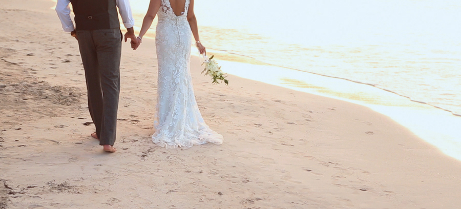 bride and groom walking on the beath at couples negril resort in jamaica