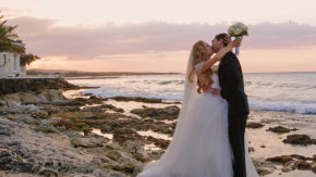 bride and groom kissing on jamaican beach